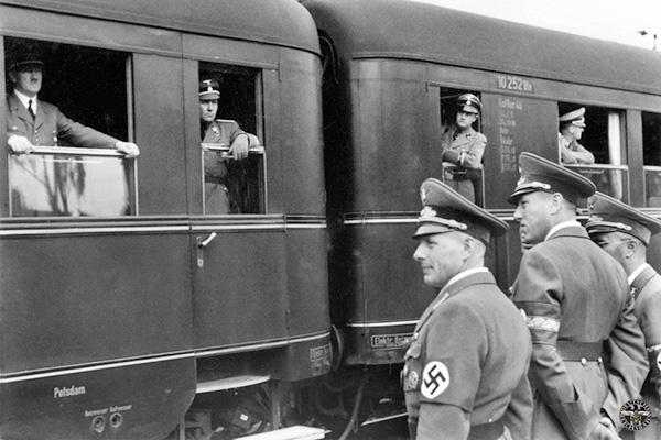Einige NS-Funktionsträger stehen am Bahnhof und verabschieden oder begrüßen einen Zug.